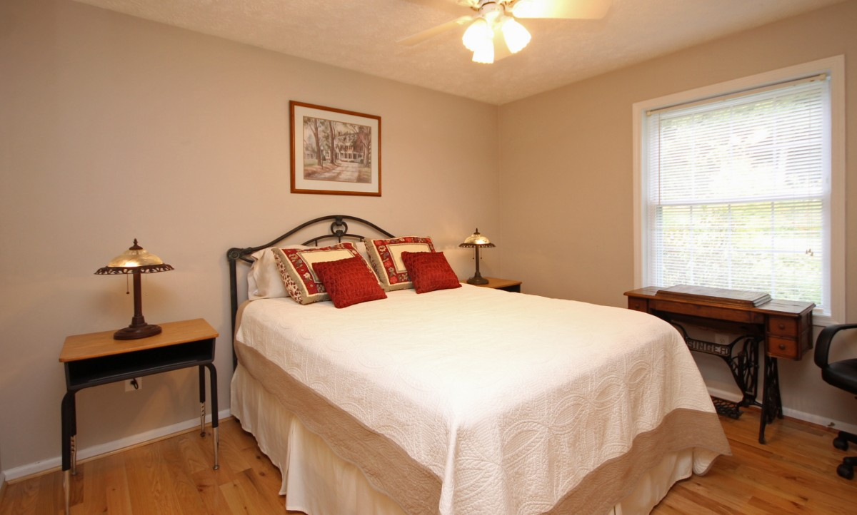 In the bright and cheerful second bedroom you will find this lovely Queen bed and repurposed school desk side tables.