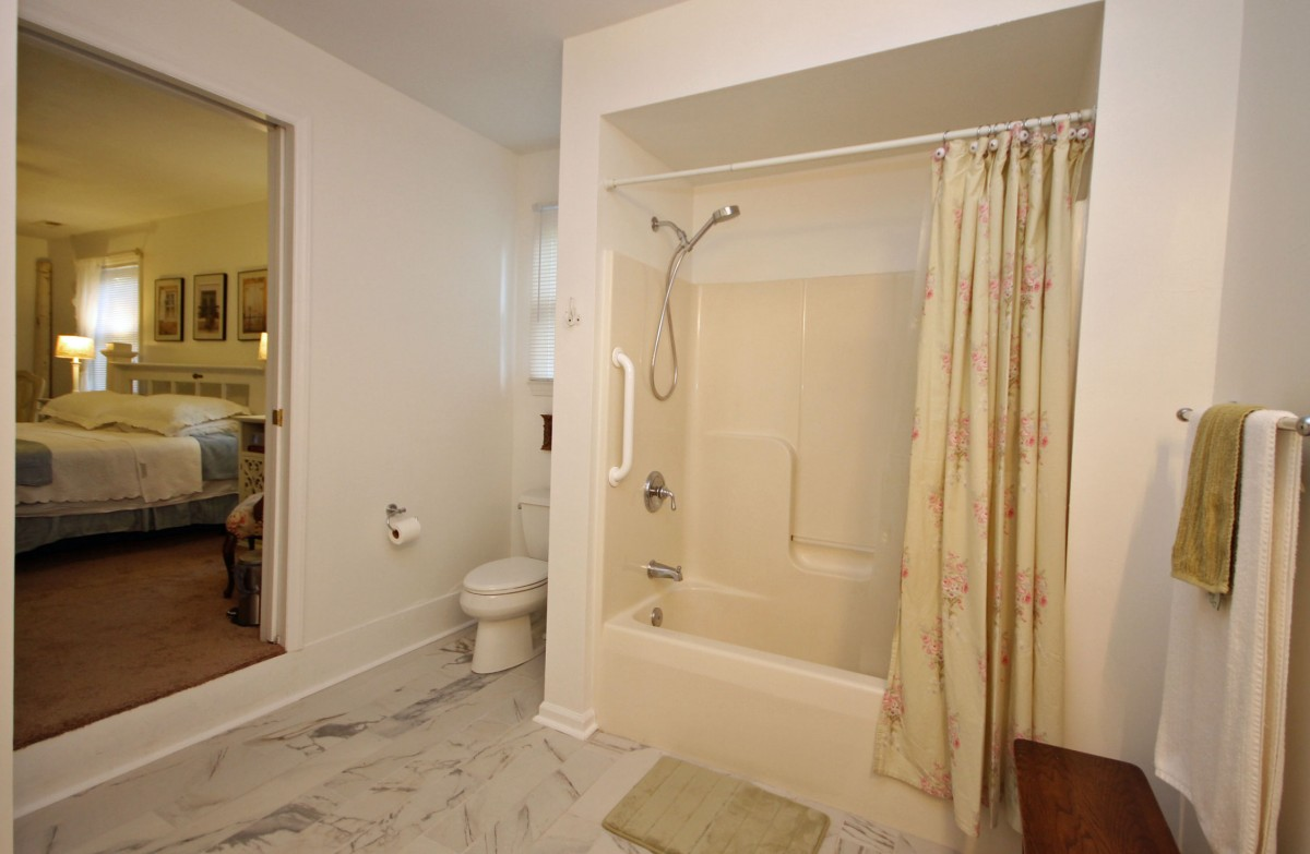 The bathroom features a roomy shower, vanity, and sitting area.
