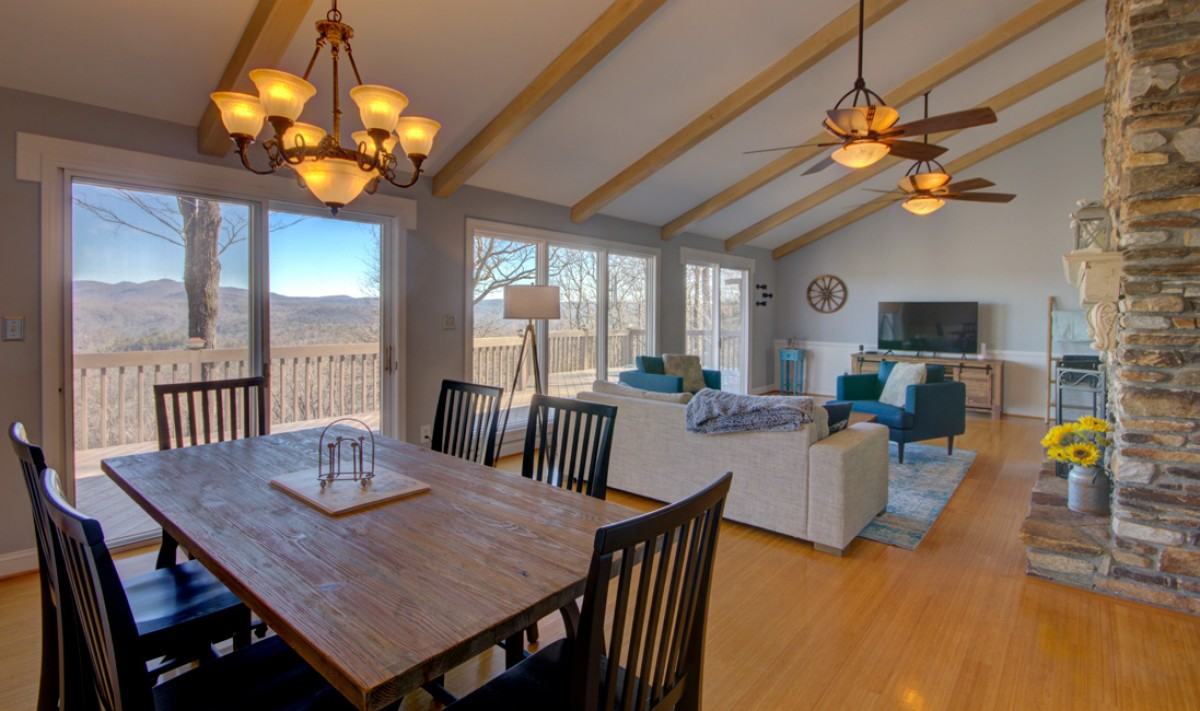 The overall view of the living room shows the dining area, the living room, the TV, the fireplace and of course the view!