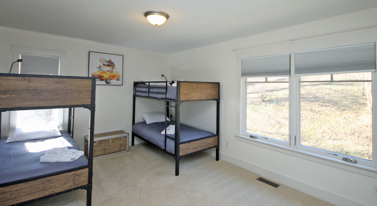 Four bunk beds, perfect for kids or larger groups. This room is on the upper level, adjacent to the second bedroom.
