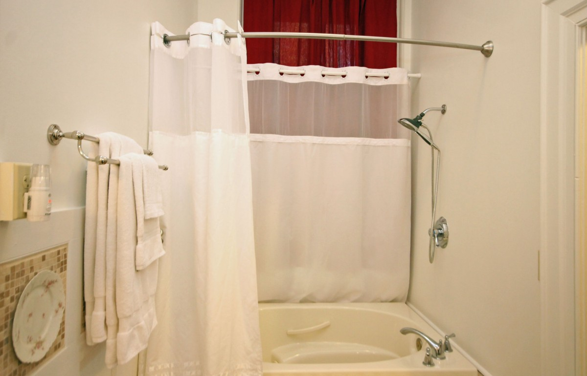 The shower curtain is hung on a curved bar that provides extra space while you shower.