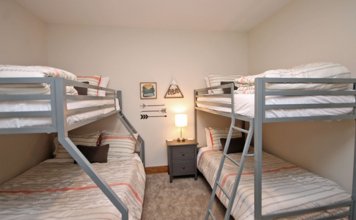 The second bedroom on the main floor features two sets of bunk beds. One Twin/Twin, the other Twin/Full