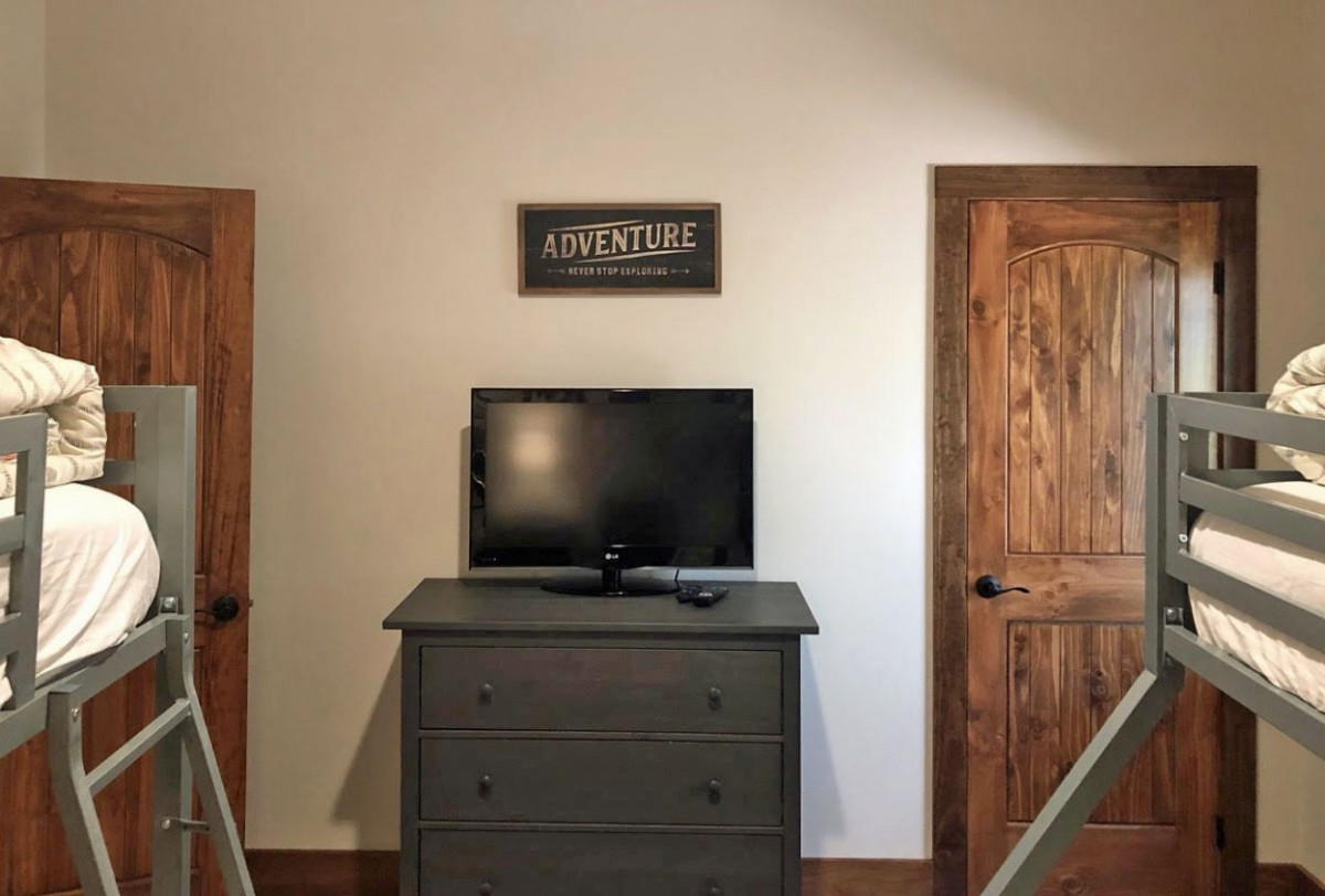 The bunk room features a TV and dresser.