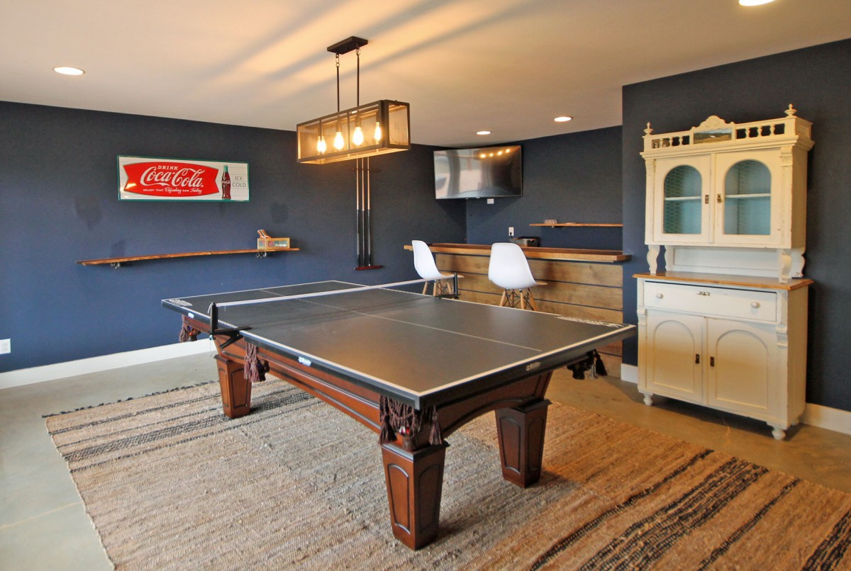 The ping pong table can be converted to a pool table, and there is a bar for entertaining in the back corner. The hot tub is just outside on the lower deck.