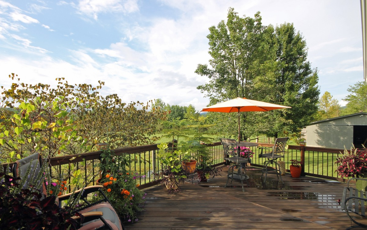The deck at the back of the house is just beside the screened porch. We love the peaceful setting, the flowers and the view.