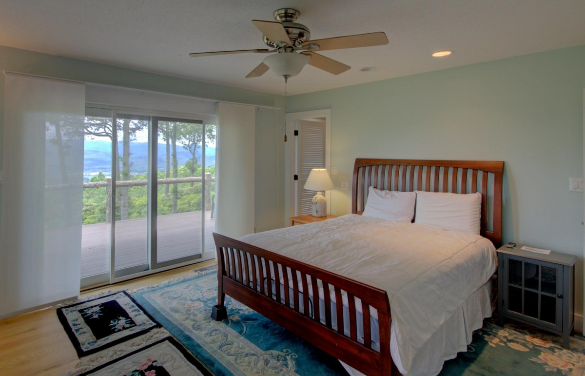 The master bedroom is on the main level and features a queen bed, a deck and a great view.