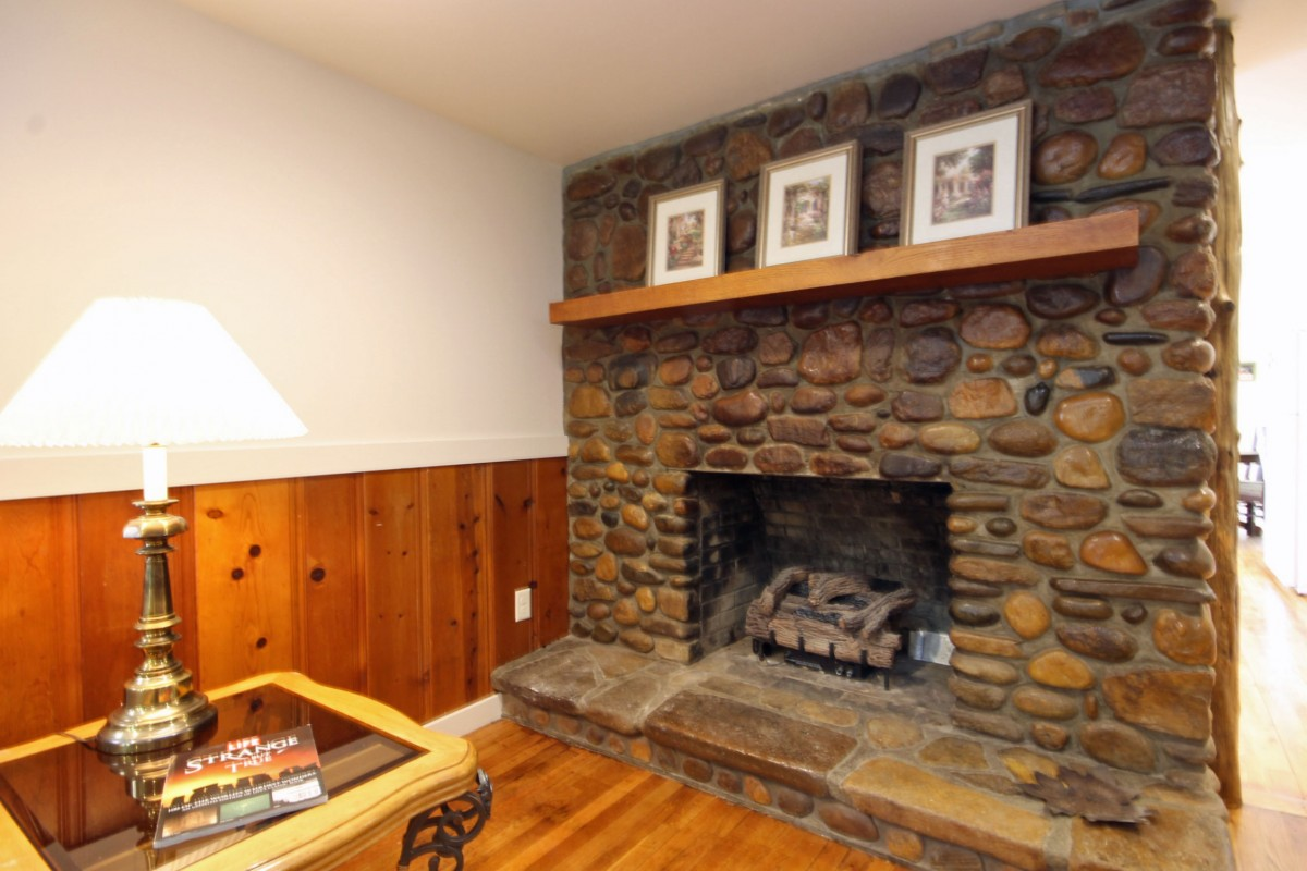 The hand built stone fireplace is the centerpiece of this home. It is out of service but lends lots of appeal.