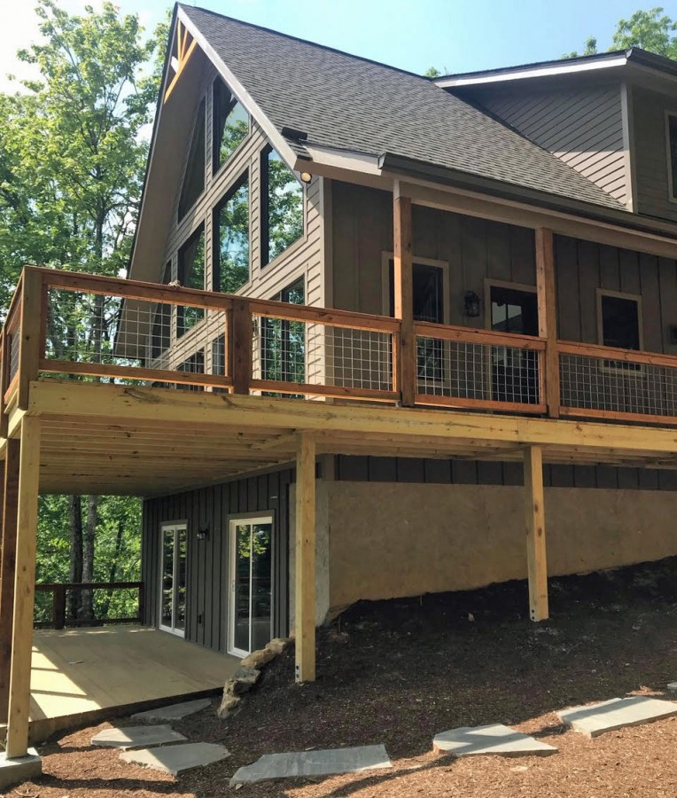 View of the covered side porch and back deck. The basement is unfinshed and owner's space. The bottom deck is only accessible from the outside.