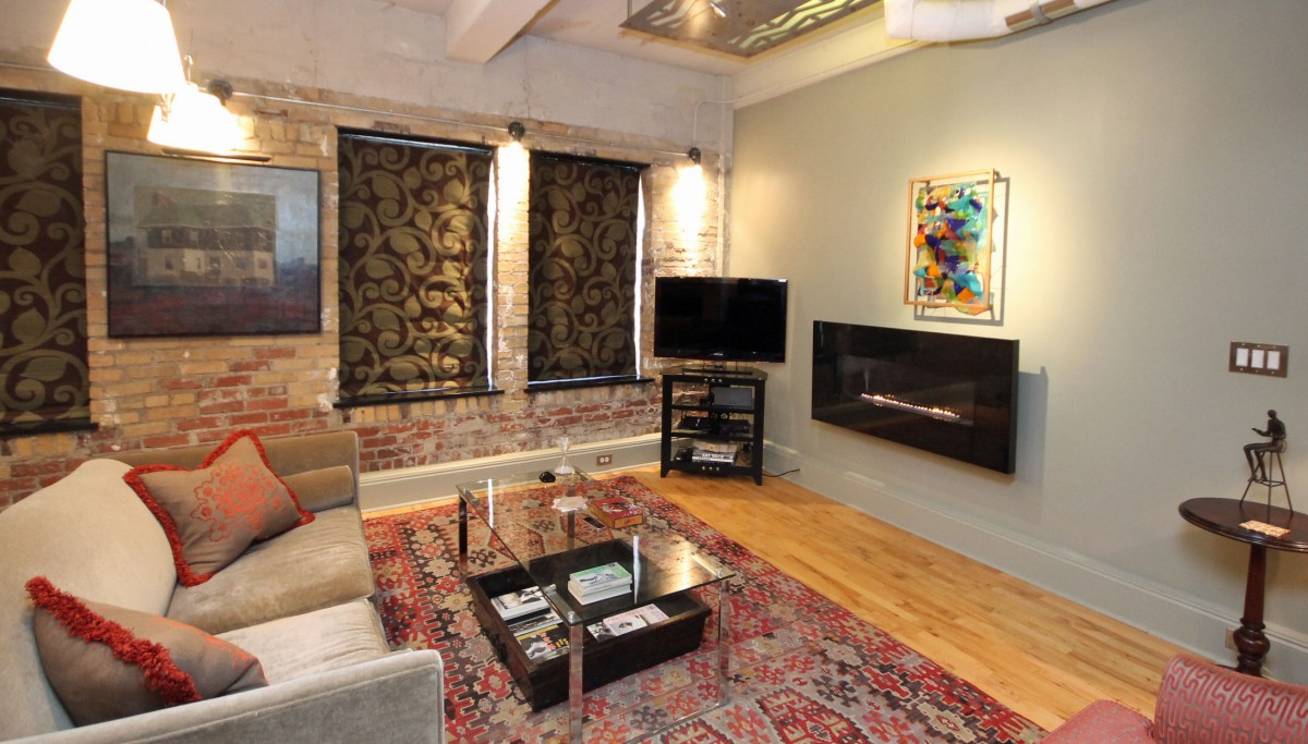A ribbon fireplace and art from local galleries add warmth and personality to this urban loft.