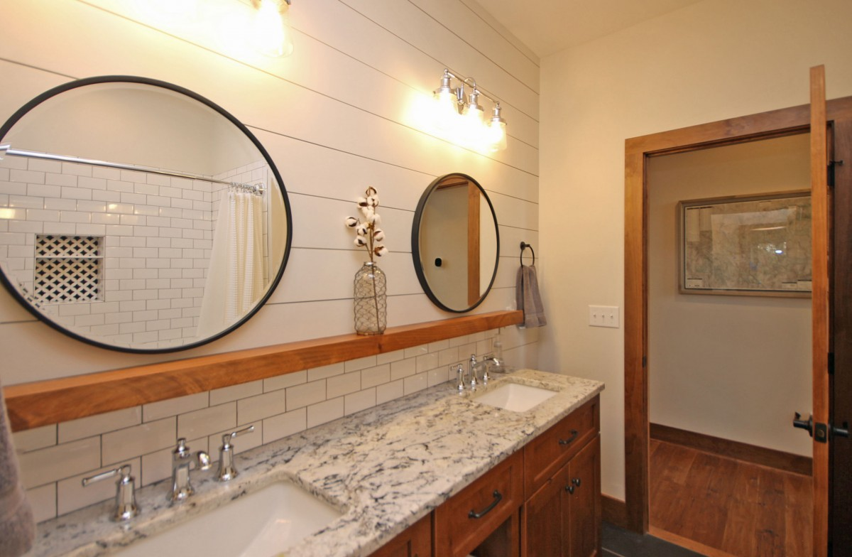 The full bath on the main floor features dual vanities and granite countertops.