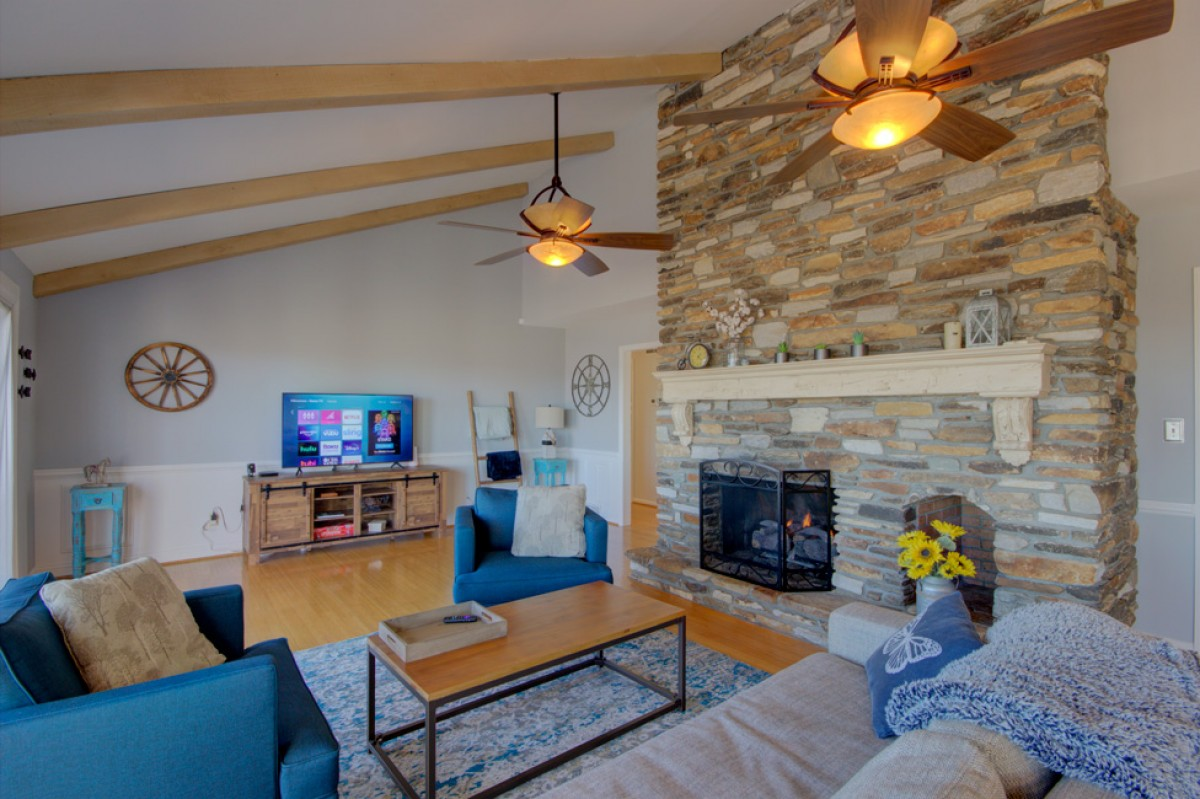 Stone fireplace with gas logs, comfy seating and big TV