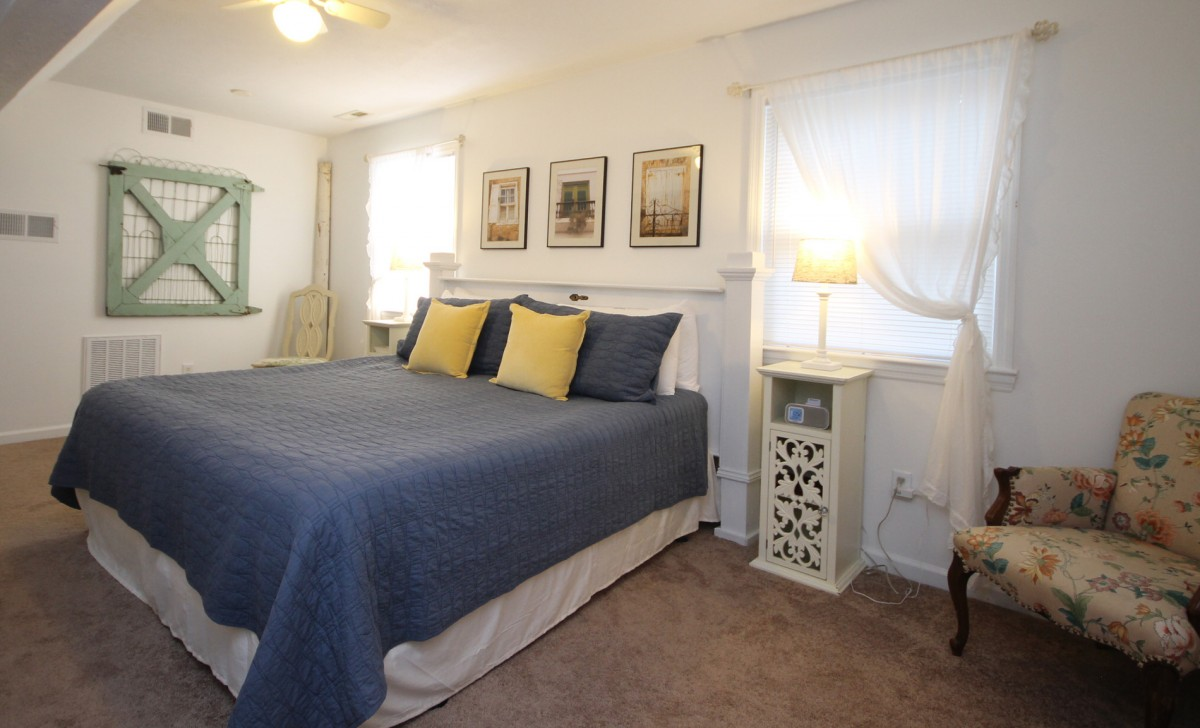 The bedroom features a comfy king bed which is warm and inviting.