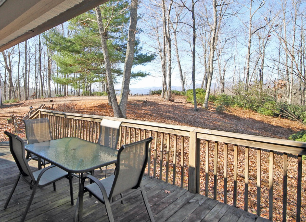 Enjoy wooded privacy on the front porch as you look at the scenic view in the background.