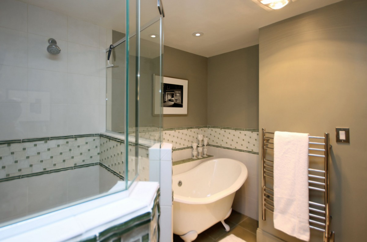 A walk-in shower, ceramic clawfoot tub, heated towel bar, lighted shaving mirror, and Sonos speaker add both function and beauty to the bathroom.
