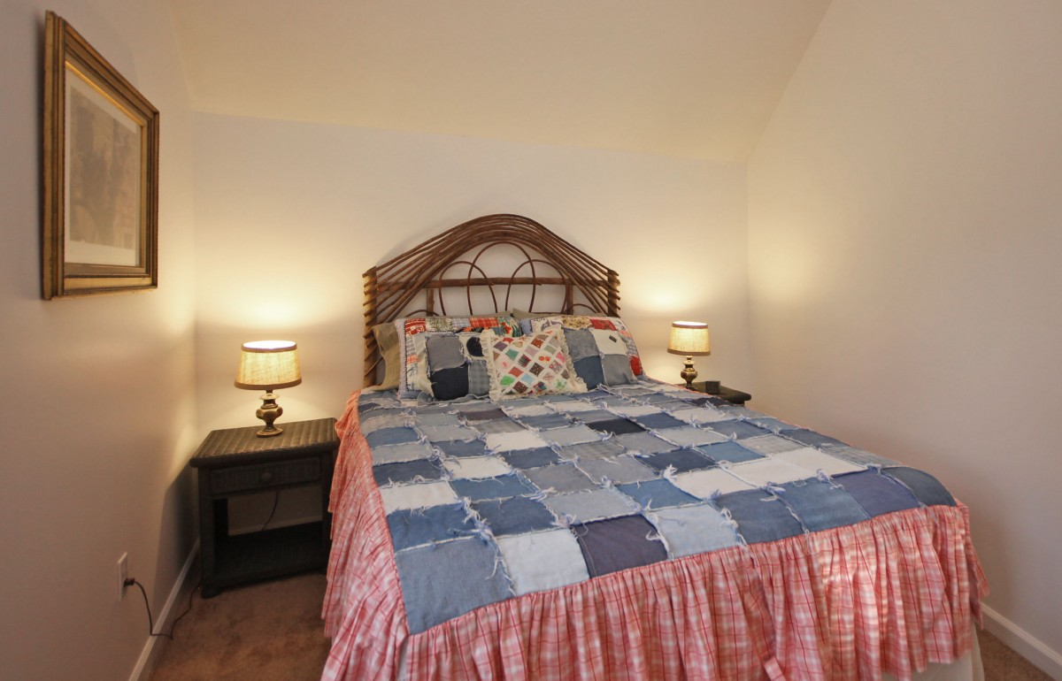 The second guest bedroom features a cozy queen bed with a whimiscal woven headboard.