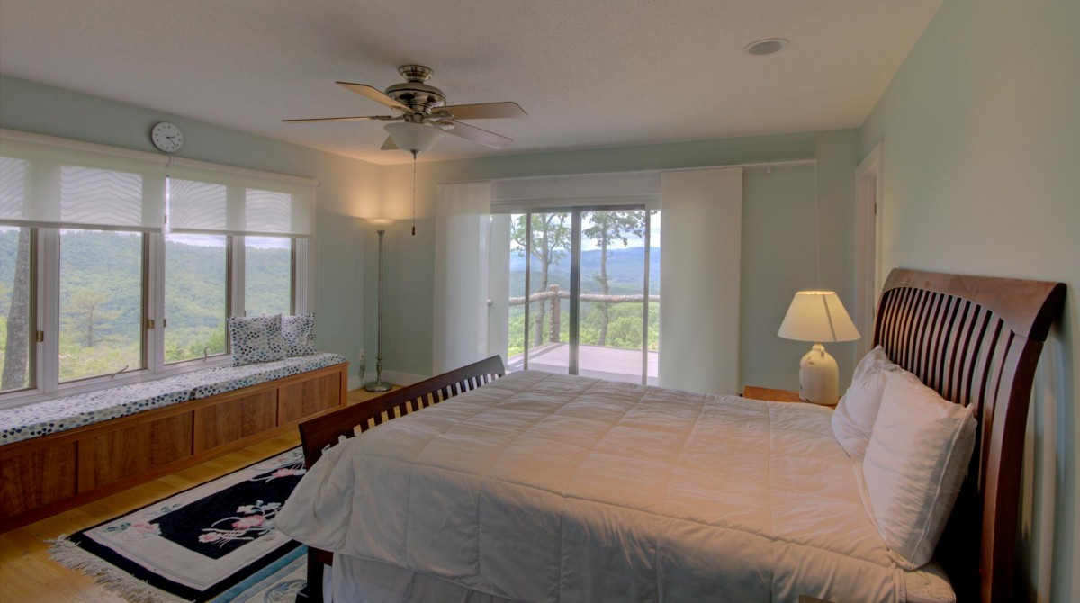The master bedroom on the main level features a queen bed and spectacular views.