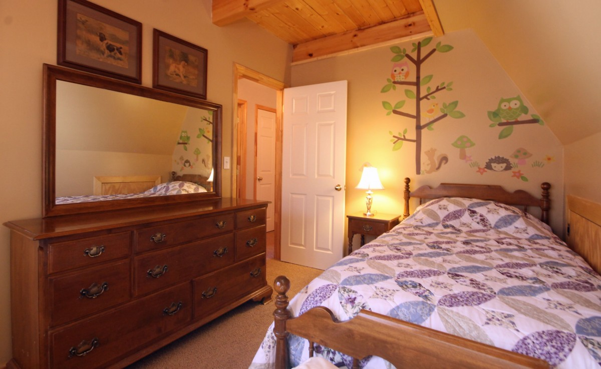 Here is the second downstairs bedroom, featuring a twin bed and whimsical walls. It's a great room for kids, and a warm inviting space.