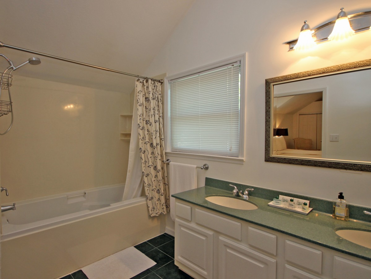 The bright, roomy bathroom features dual vanities. The bathroom is accessible only through the master bedroom so please be aware of this before booking.