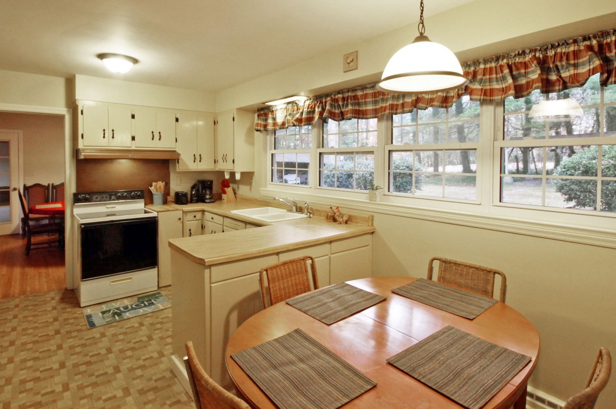 The sunny, bright kitchen features a cozy breakfast nook.