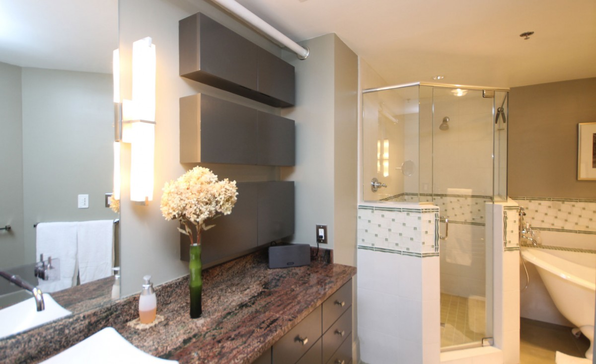 Granite counters, custom cabinets and tilework, and faucet mounted into the mirror are added features in the bathroom.