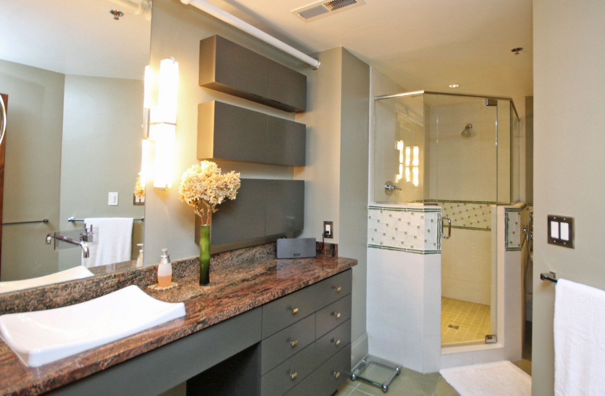 Entering the bathroom, you will find custom cabinetry, tile, and lighting, with plenty of room for storing personal items.