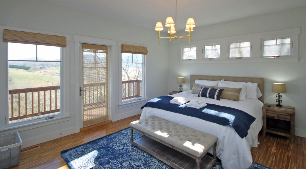 The master bedroom is on the main level. It features a comfy king bed, lots of windows, access to the upper deck and a beautiful view.