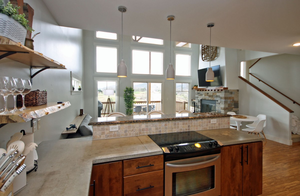 From the kitchen you can see the living area leading out to the lower deck which features a grill and sitting area.